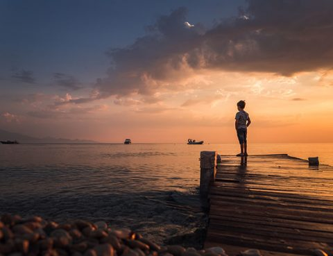 Child enjoying the sunrise standing on a wooden pier & looking a